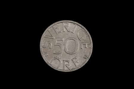 A close up, macro image of an old Swedish fifty ore coin isolated on a black background