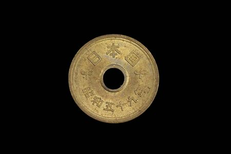 A close up, macro image of golden, Japanese five yen coin isolated on a black background