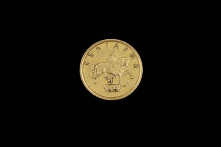 A close up image of a gold one stotinki coin from Bulgaria, shot in macro, on a solid black background