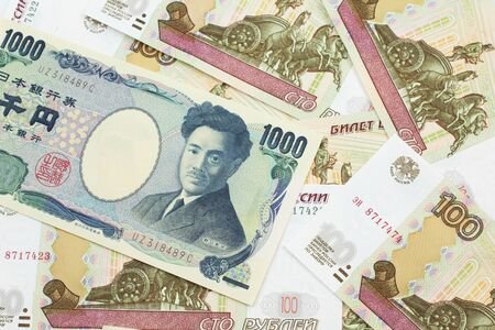 A one thousand Japanese yen bank note close up in macro with Russian one hundred ruble bills
