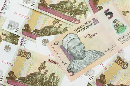 A close up image of a peach colored, five Nigerian naira bank note on a background of Russian one hundred ruble bank notes Archivio Fotografico