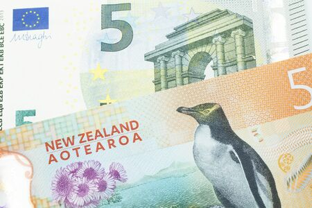 A close up image of a purple, five Australian dollar note close up, in macro with a five euro note from the European Union