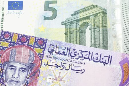 A multicolored one rial note from Oman, close up in macro with a blue and green five Euro bill Archivio Fotografico