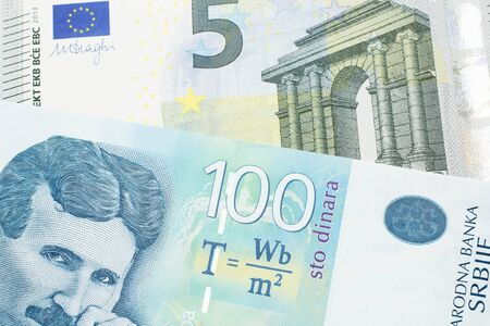 A blue one hundred Serbian dinar bank note, close up in macro with a red, European Union five euro bank note