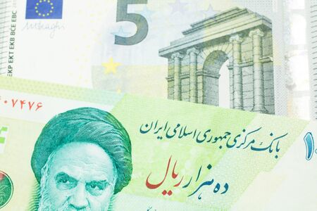 A close up image of a green Iranian ten thousand rial bank note with a blue and green five euro note from France in macro Archivio Fotografico