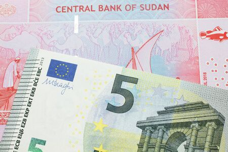 A five Euro, European Union bill with a fifty pound note from Sudan close up in macro