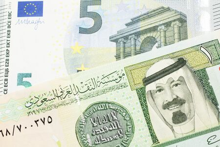 A green one riyal bank note from Saudi Arabia with a blue and green five euro bank note close up in macro