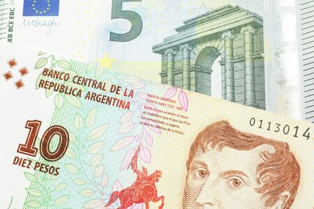 A ten peso bill from Argentina, close up in macro with a red, five Euro European bank note Stock Photo