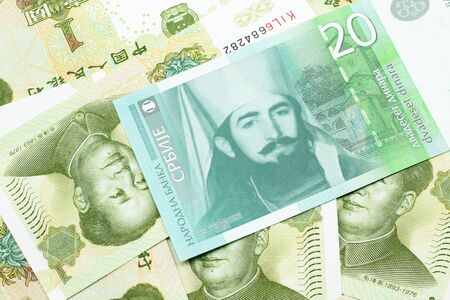 A close up of a green and white, twenty Serbian dinar bank note on a background of Chinese one yuan bank notes