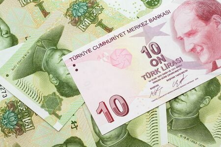 A close up image of a red ten Turkish lira bank note on a background of Chinese one yuan bank notes in macro Stock Photo
