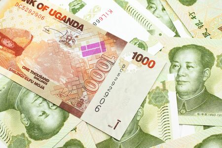 A close up image of a colorful Ugandan shilling bank note with Chinese one yuan bills in macro Stock Photo