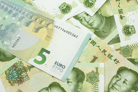 A close up image of a five Euro bank note from Europe in macro with a bed of Chinese one yuan bank notes