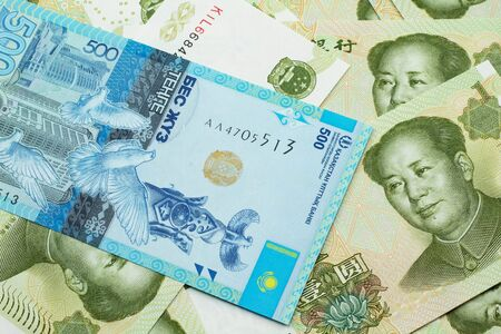 A blue five hundred tenge note from Kazakhstan with Chinese one yuan bills close up in macro