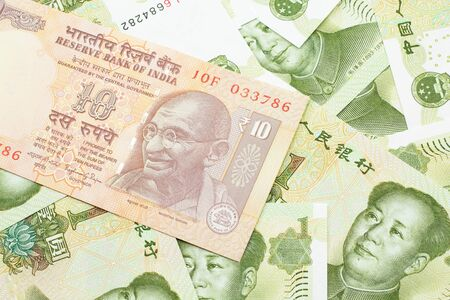 A close up image of an orange ten Indian rupee bank note in macro on a bed of Chinese one yuan bank notes 스톡 콘텐츠
