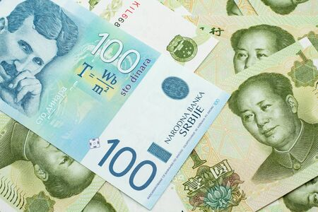 A close up of a blue and white, one hundred Serbian dinar bank note on a background of Chinese one yuan bank notes