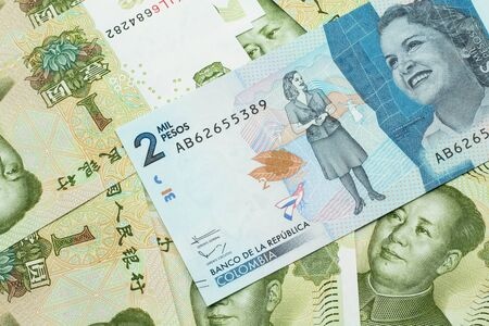 A close up image of a blue two thousand Colombian peso bank note on a background of Chinese one yuan bank notes in macro Stock Photo