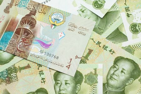 A colorful quarter dinar bank note from Kuwait close up in macro with Chinese one yuan bills