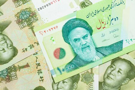 A macro image of a green ten thousand rial bank note from Iran on a bed of Chinese one yuan bank notes close up