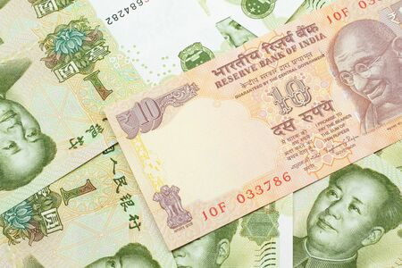 A close up image of an orange ten Indian rupee bank note in macro on a bed of Chinese one yuan bank notes Stock Photo