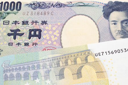 A one thousand Japanese yen bank note, close up in macro with a five Euro European bank note