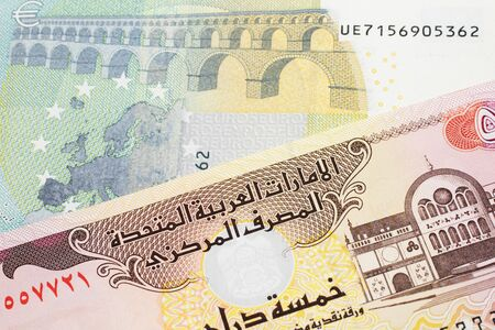 A blue and green, European five euro bank note with a five dirham bank note from the United Arab Emirates close up in macro
