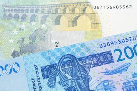 A close up image of a blue, West African franc bank note with a five Euro bank note in macro