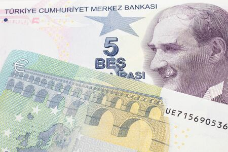 A close up image of a purple five Turkish lira bank note with a German five euro bill in macro
