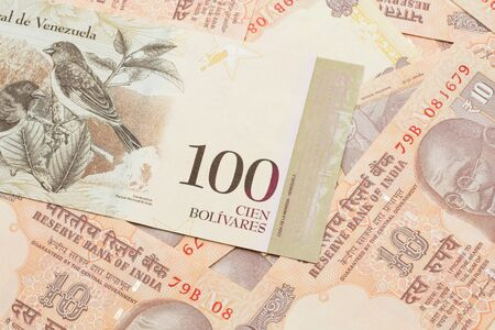 A Venezuelan one hundred Bolivares bank note, close up in macro on a bed of Indian ten rupee bank notes
