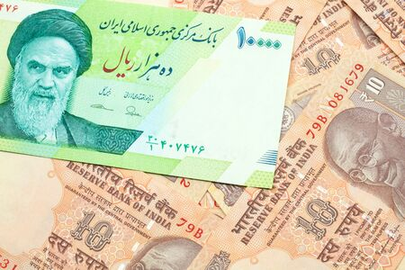 A macro image of a green ten thousand rial bank note from Iran on a bed of Indian ten rupee bank notes close up Archivio Fotografico