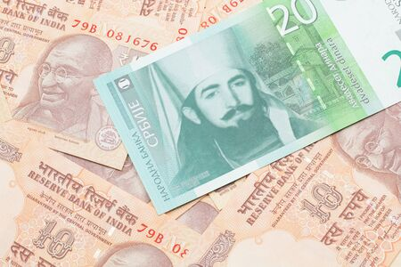 A close up of a green and white, twenty Serbian dinar bank note on a background of Indian ten rupee bank notes
