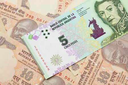 A five peso bank note from Argentina on a background of Indian ten rupee bank notes close up