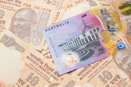 A close up image of an Australian five dollar bill with Indian ten rupee bank notes in macro 版權商用圖片