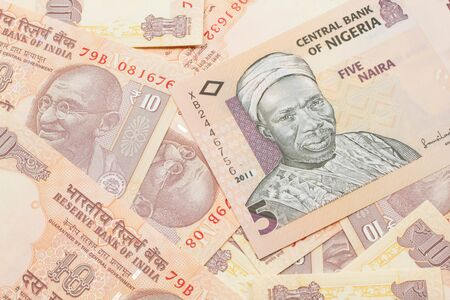 A close up image of a peach colored, five Nigerian naira bank note on a background of Indian ten rupee bank notes