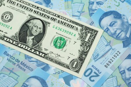 A close up image of a an American one dollar bank note with Mexican twenty peso bank notes in macro