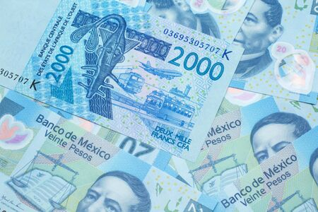 A close up image of a blue, two thousand, West African franc bank note in macro on a background of United States Mexican twenty peso bills