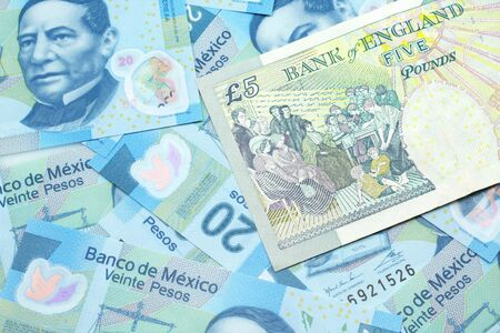 A close up image of a multicolored five pound note from the United Kingdom on a background of Mexican twenty peso bank notes in macro