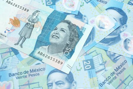 A close up image of a blue two thousand Colombian peso bank note on a background of Mexican twenty peso bank notes in macro Stock Photo