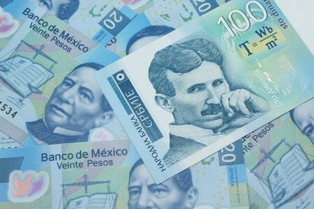 A close up of a blue and white, one hundred Serbian dinar bank note on a background of Mexican twenty peso bank notes