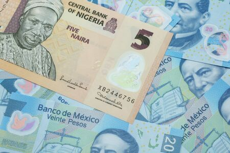 A close up image of a peach colored, five Nigerian naira bank note on a background of Mexican twenty peso bank notes Stock Photo