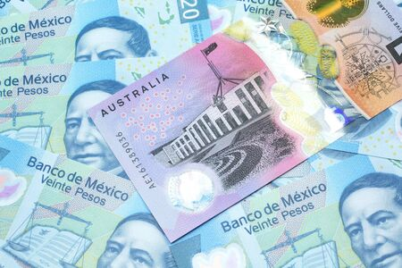 A close up image of an Australian five dollar bill with Mexican twenty peso bank notes in macro