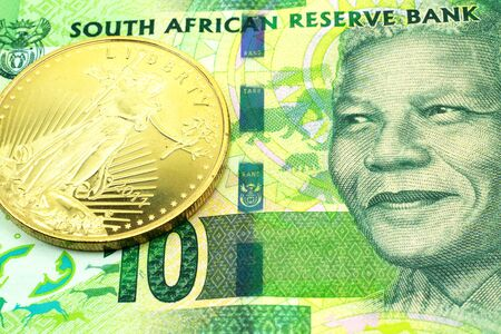 A macro image of a green ten rand note from South Africa with a gold coin.  Shot close up.