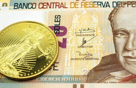 A macro image of a twenty Peruvian soles banknote with a gold coin.  Shot close up.