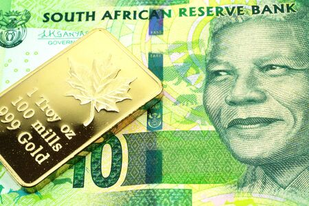 A macro image of a green ten rand note from South Africa with a gold bar.  Shot close up.