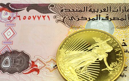 A macro image of a 5 dinar banknote from the United Arab Emirates with a gold coin.  Shot close up. Stock Photo