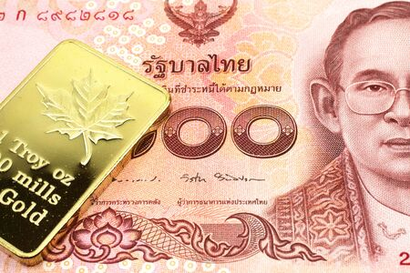 A macro image of a red one hundred Thai baht note with a gold bar.  Shot close up.