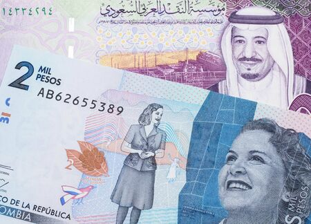 A colorful five Saudi riyal bank note with a blue two thousand peso note from Colombia close up in macro