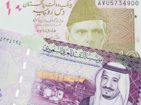 A pink and grey ten Pakistani rupee bank note with a five Saudi riyal bank note in macro