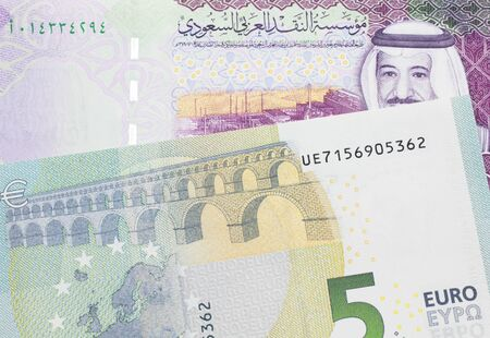A green and yellow five Euro bank note from the EU with a colorful five riyal bank note from Saudi Arabia close up in macro Stock Photo