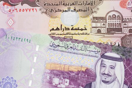 A colorful, five Saudi riyal bank note with a five dirham bank note from the United Arab Emirates close up in macro