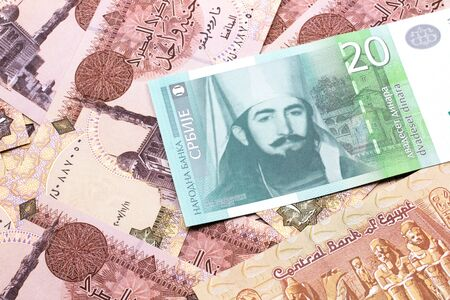 A close up of a green and white, twenty Serbian dinar bank note on a background of Egyptian one pound bank notes 写真素材